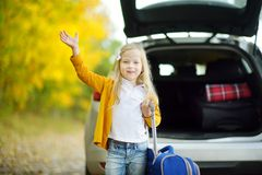 Adorable girl with a suitcase ready to go on vacations with her parents. Child looking forward for a road trip or travel. Autumn b. Reak at school. Traveling by Stock Photo