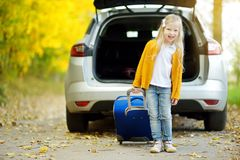 Adorable girl with a suitcase ready to go on vacations with her parents. Child looking forward for a road trip or travel. Autumn b. Reak at school. Traveling by Stock Photography