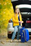 Adorable girl with a suitcase ready to go on vacations with her parents. Child looking forward for a road trip or travel. Autumn b Royalty Free Stock Photo
