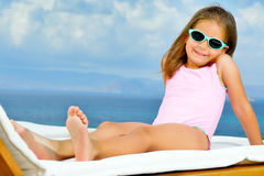 Adorable girl on sunbed. Adorable toddler girl relaxing on sunbed Royalty Free Stock Photo