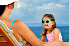 Adorable girl on sunbed. Adorable toddler girl relaxing on sunbed with her mother Stock Images