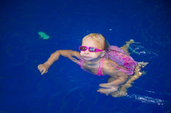 Adorable girl in sunglasses swim alone in pool near ladder Stock Images