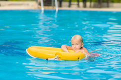 Adorable girl swim in pool with life ring in tropical beach reso Stock Photo