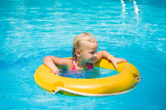 Adorable girl swim on yellow life ring in pool at protical beach Royalty Free Stock Photo
