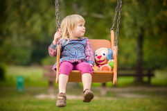 Adorable girl swing with plush toy on playground Royalty Free Stock Images