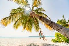 Adorable girl swinging. Adorable girl having fun swinging at tropical island beach royalty free stock images
