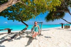 Adorable girl swinging. Adorable girl having fun swinging at tropical island beach stock photo