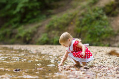 Adorable girl throw stone to river stream in park Stock Photography