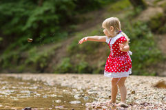 Adorable girl throw stone to river stream in park Stock Images