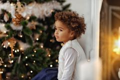 Adorable girl waiting for Santa. Cheerful toddler girl in front of the Christmas tree Stock Photo