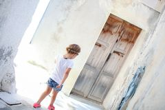 Adorable girl walking alone in narrow streets of Royalty Free Stock Photos