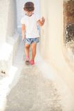 Adorable girl walking alone in narrow streets of Royalty Free Stock Image
