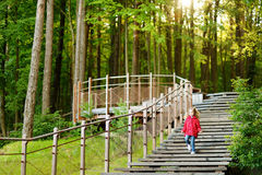 Adorable girl walking down stairs in summer park. On beautiful sunny day Royalty Free Stock Photo