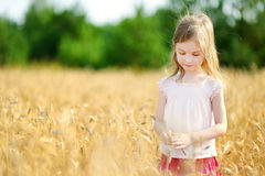 Adorable girl walking happily in wheat field Royalty Free Stock Photos