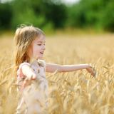 Adorable girl walking happily in wheat field Royalty Free Stock Image