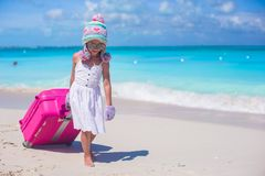 Adorable girl in warm winter hat and mittens walking with luggage on beach Royalty Free Stock Photography