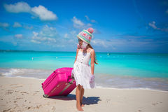 Adorable girl in warm winter hat and mittens walking with luggage on beach Royalty Free Stock Photo