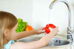 Adorable girl washing vegetables in a kitchen Royalty Free Stock Photography