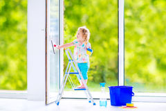 Adorable girl washing a window in white room Royalty Free Stock Photos