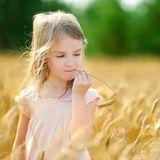 Adorable girl in wheat field on warm summer day Royalty Free Stock Photography