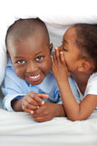 Adorable girl whispering something to her brother Stock Images