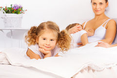 Adorable girl on white bed with mother feeding son stock image
