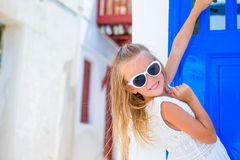 Adorable girl in white dress outdoors in old streets an Mykonos. Kid at street of typical greek traditional village with Stock Photography