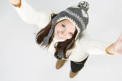 Adorable girl in winter clothes looking up with raised arms. Stock Photos