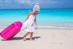 Adorable girl in winter hat and mittens walking with luggage on beach Stock Image