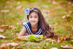 Adorable girl with yellow leaves lies Stock Photos