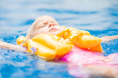 Adorable girl with yellow life vest in pool in tropical beach re Royalty Free Stock Photo