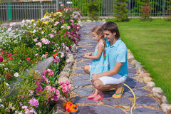 Adorable girl and young father watering flowers Stock Photo