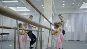 Adorable girls practice with teacher in ballet studio. Two girlie stand and hold on to handrails with hands and then go up to toes and raise arms, copying stock video footage