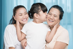 Adorable granddaughter. Close-up image of an adorable granddaughter bonding her mother and kissing her grandparent at home Stock Image