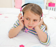Adorable gril listening to music lying on her bed Stock Photography