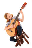 Adorable Guitar Girl. Adorable 7 year old blond girl playing acoustic guitar over white background stock images