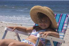 Adorable Hannah. A pretty little girl sits in a chair at the beach royalty free stock photo