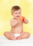 Adorable happy baby with apple Stock Photos