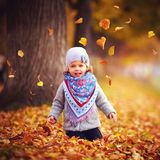 Adorable happy baby girl catching the fallen leaves, playing in the autumn park Stock Photo