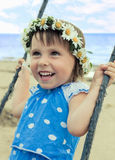 Adorable happy baby girl swinging on a swing at the seaside Royalty Free Stock Photography