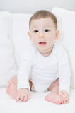 An adorable, happy baby looking at camera on white pillows Royalty Free Stock Image