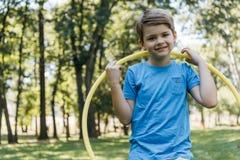 adorable happy boy holding hula hoop and smiling at camera stock image