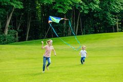 Adorable happy brother and sister playing with kite on green meadow. In park stock image