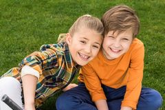 Adorable happy brother and sister sitting together on green grass and smiling royalty free stock photo