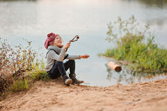 Adorable happy child girl plays with stick on river side in summer day Stock Photo