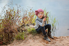 Adorable happy child girl plays with stick on river side in summer day Stock Images