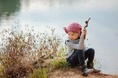 Adorable happy child girl plays with stick on river side in sunny day royalty free stock images