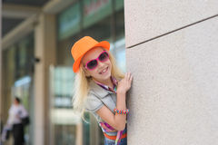 Adorable happy child in sunglasses. And orange hat. Shop windows in the background. and orange hat. Shop windows in the background. Girl peeking around the Stock Photos