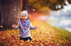 Adorable happy girl throwing the fallen leaves up, playing in the autumn park Stock Photography