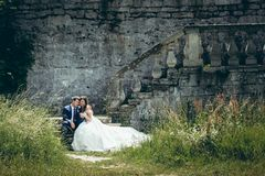 Adorable happy just married couple holds hands and sits on the old strairs of the castle. Beautiful nature view. Adorable happy just married couple holds hands Royalty Free Stock Image